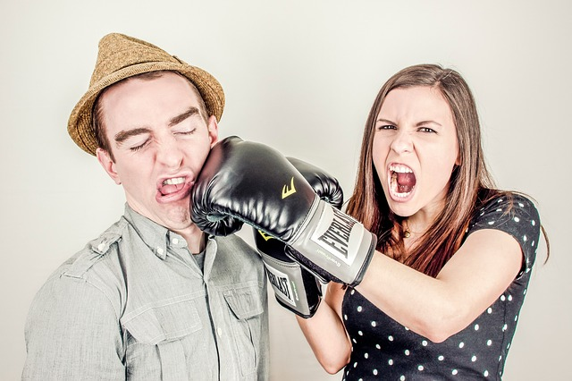 Conflict - Woman punching man with boxing glove